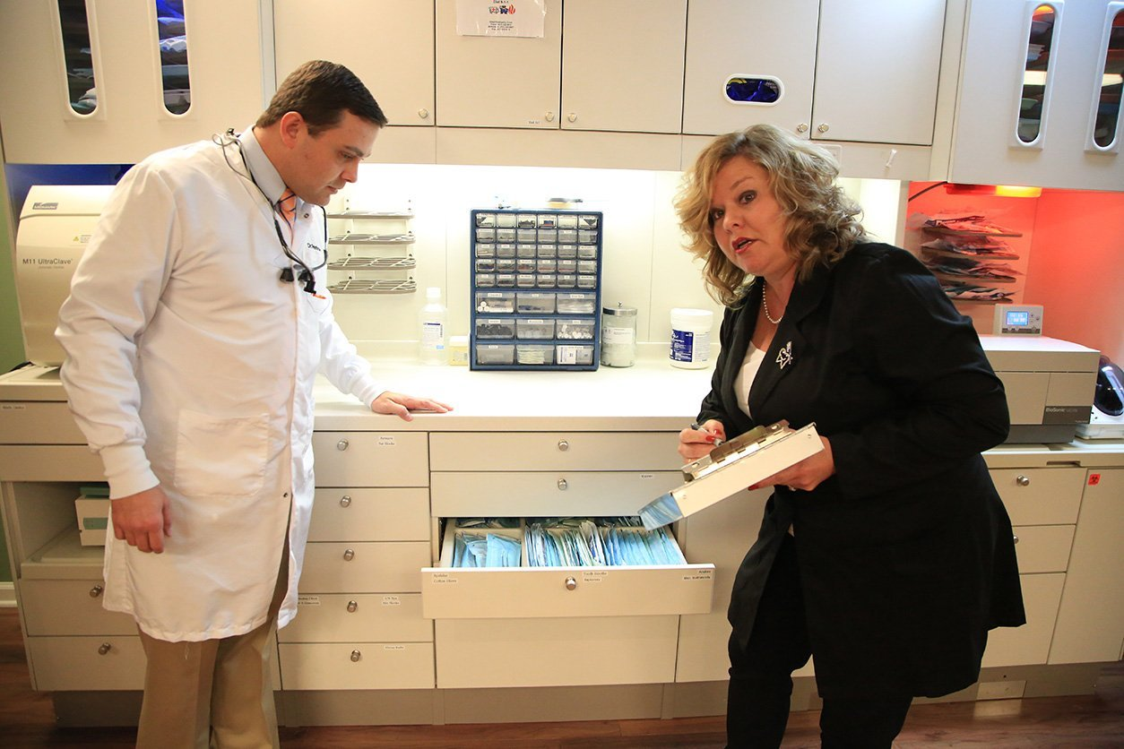 Olivia explaining something to doctor and staff member while looking in drawer
